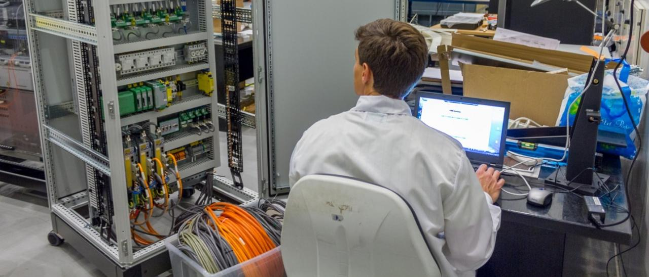Image of an engineer working on the electronics of the adaptive optics system for GTC in the laboratory. Engineer sitting working on a computer with an open electronics cabinet at his side