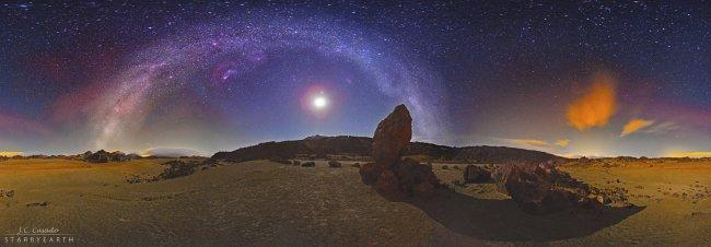 "Starry night from the Teide National Park (Tenerife, Spain). We can see Mount Teide, near the centre of the picture, and the Moon within the arch of the Milky Way, behind a volcanic landscape with large rocks in the region of ""The San José Mines"". An unco"