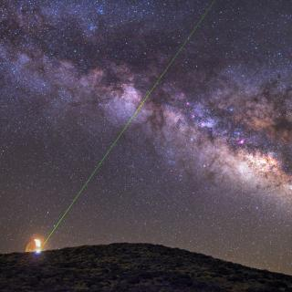 Night image of the Milky Way and the emission of a green laser from the OGS during tests of communications with La Palma. Author Daniel López.
