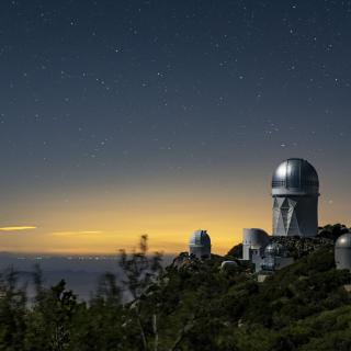 A view of the Mayall Telescope (tallest telescope at right) at Kitt Peak National Observatory near Tucson, Arizona. (Credit: Marilyn Chung/Berkeley Lab)