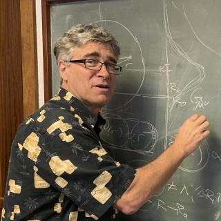 Jeffrey R. Kuhn, writing on a blackboard during his visit the IAC.