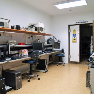 General view of the Electromagnetic Compatibility Laboratory with workbenches and computers and view in the background of the entrance to the shielded room