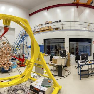 Panoramic view of one the areas of the Assembly, Integration and Verification room. Large laboratory with work benches and multiple electronic devices and computers, with a large mechanical structure in assembly phase