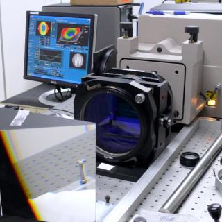 View of the interferometer on a optical table in the laboratory. Optoelectronic device with in front of a large prism and a lens with a computer monitor with graphics on the back